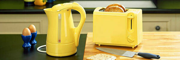 Yellow electric kettle and toaster on kitchen bench.