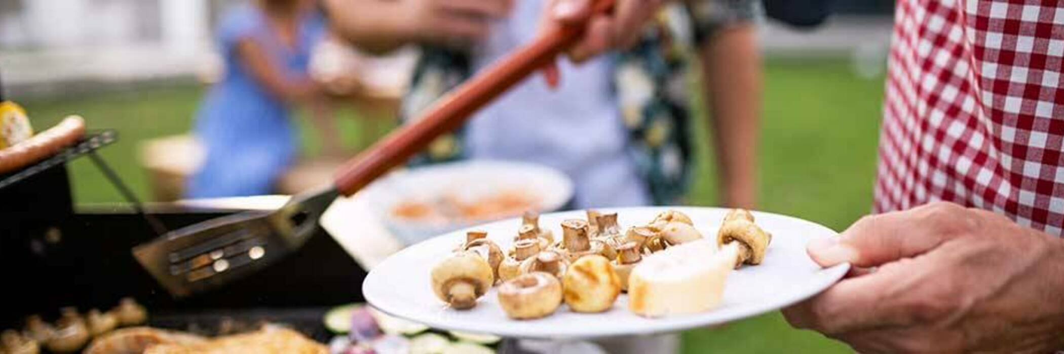Man barbecuing a plate of mushrooms.