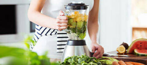 Woman preparing vegan smoothie with rocket, citrus and cucumber in the kitchen.
