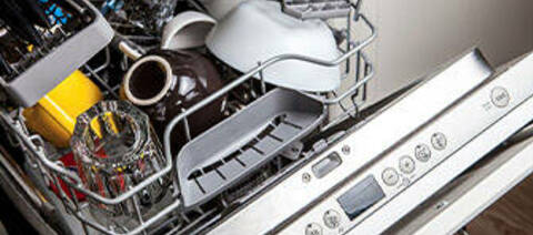 Photo of an open dishwasher with dishes inside.