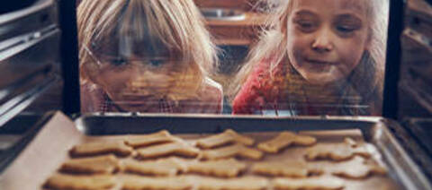 Kids checking cookies in the oven.