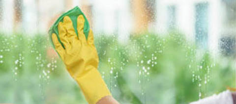 Photo of a person cleaning sprayed window.