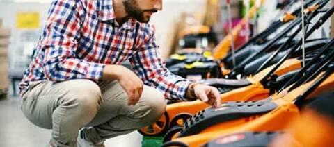 Man looking at orange lawnmower.