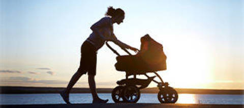 Photo of woman with a stroller by the beach.