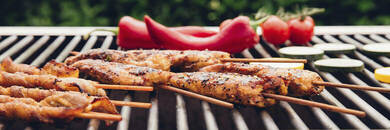 Meat kebabs, red peppers and tomatoes on barbecue.