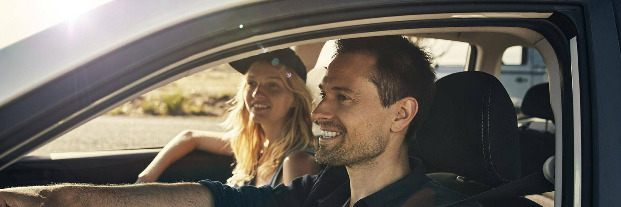 Happy man and woman in car.