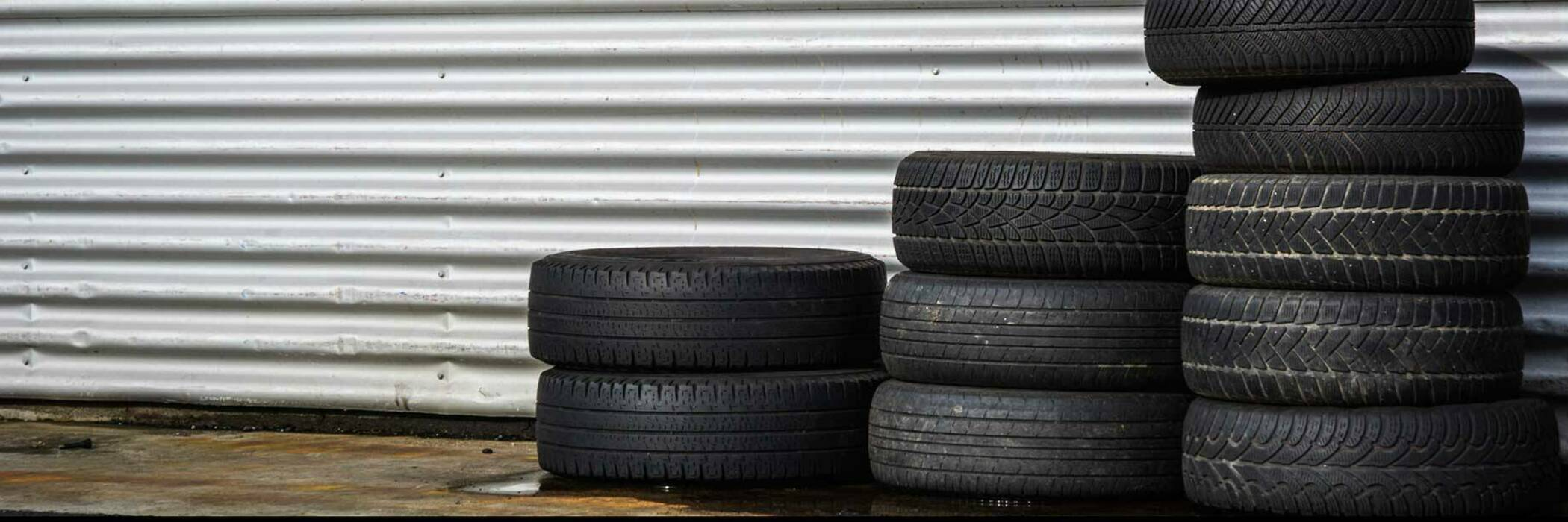 Photograph of a pile of tyres outside a garage.