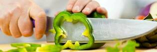 Cutting a green capsicum with a kitchen knife.