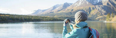 Woman using a camera to take a photo of a lake and mountains.