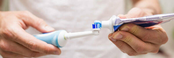 Man putting toothpaste onto electric toothbrush