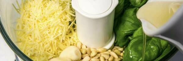 food processor bowl with basil pesto ingredients