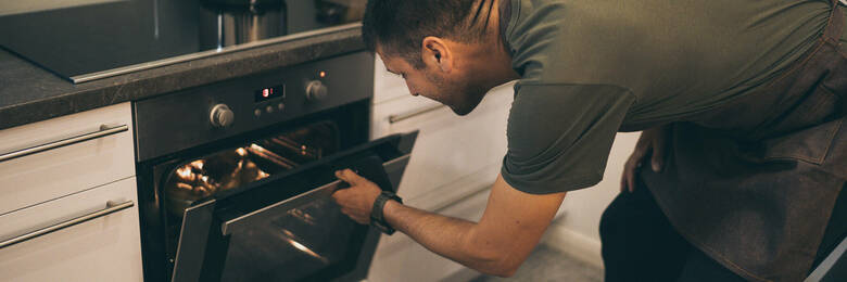 Man checking food in the oven.