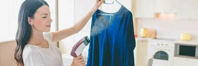 Woman using garment steamer on blue shirt.