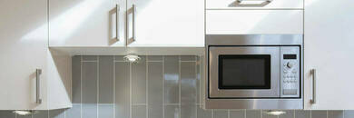 Microwave embedded in kitchen cabinet.
