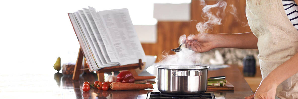 Checking pot of steaming food.