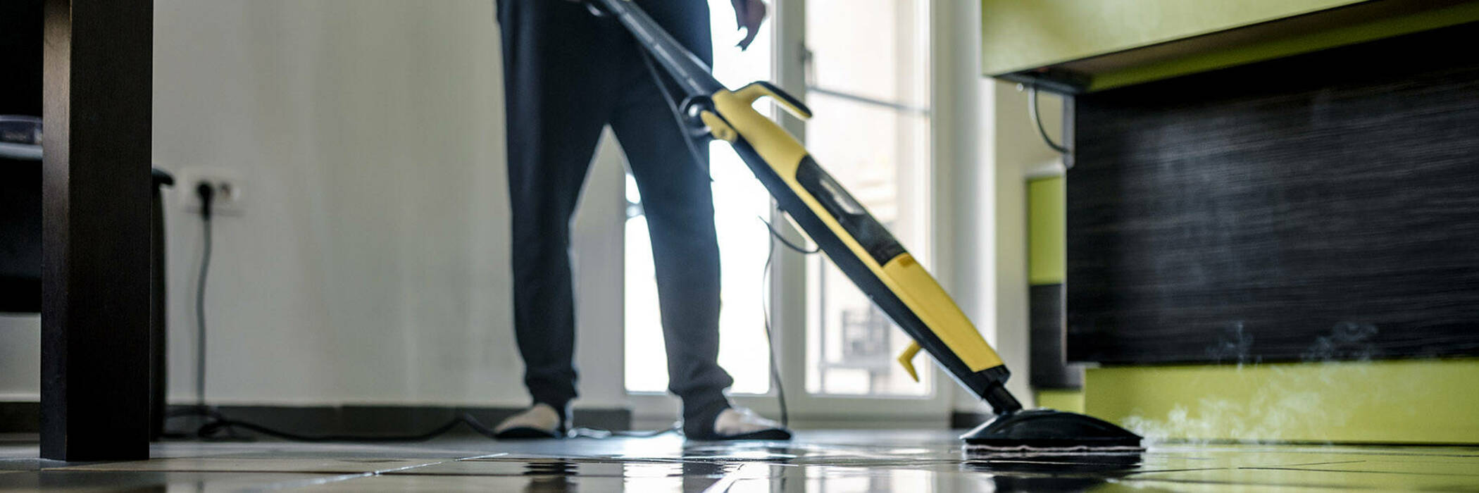 Man cleaning floor with steam mop.
