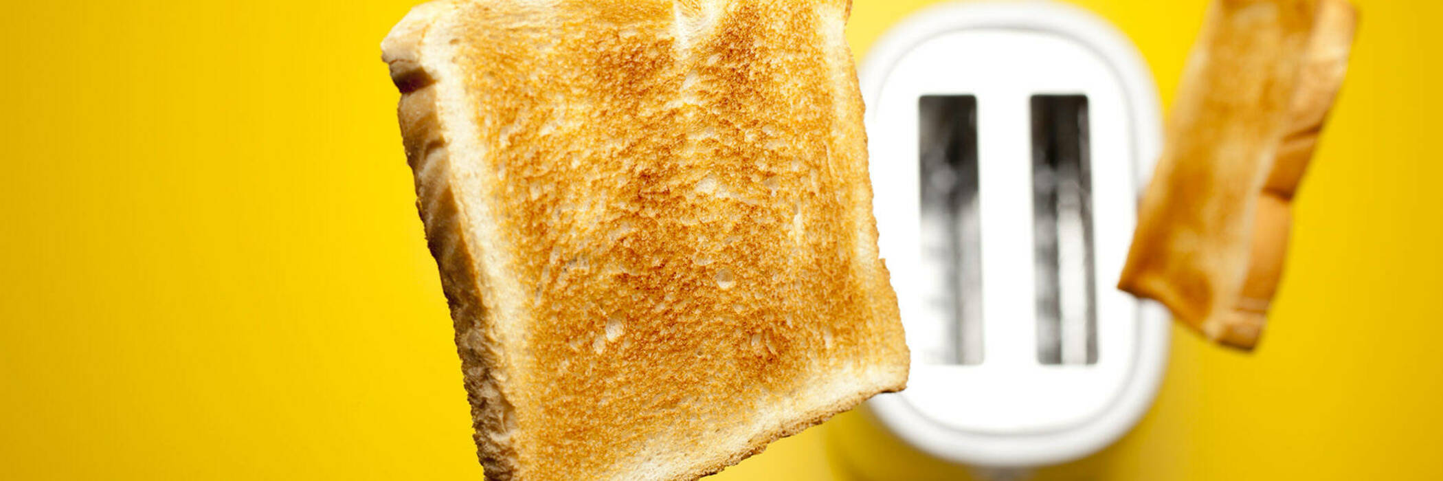 Toast popping out of white toaster.