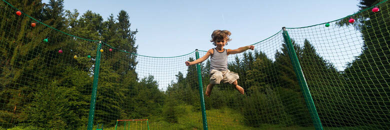 Cute kid enjoys jumping and bouncing on trampoline outdoors.