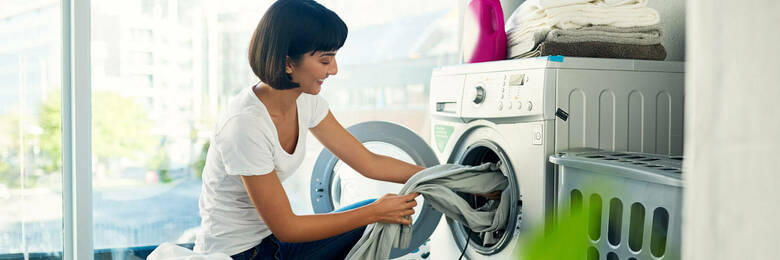 Woman removing laundry from washing machine.